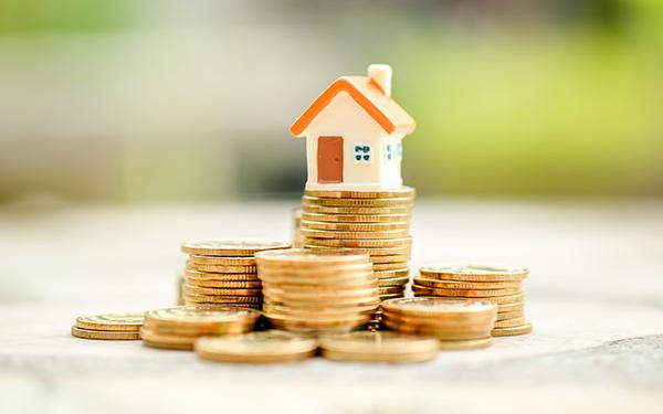 kleines Häuschen steht auf Geldmünzenstapel