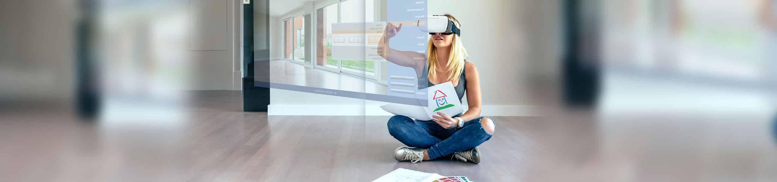 eine Frau sitzt auf dem Boden und besichtigt durch eine VR-Videobrille eine Immobilie online.